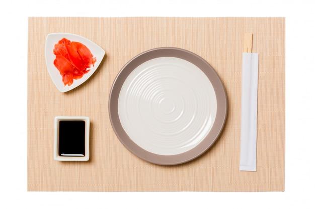 Pusty okrągły biały talerz z pałeczkami do sushi