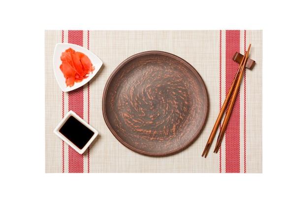 Pusty okrągły brązowy talerz z pałeczkami do sushi i sosem sojowym, imbir na tle mat sushi. widok z góry z miejscem na kopię do projektowania.