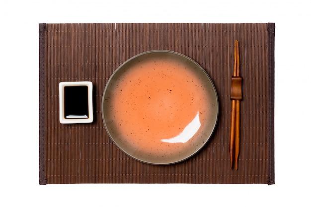 Pusty okrągły brązowy talerz z pałeczkami do sushi i sosu sojowego na ciemnej bambusowej macie
