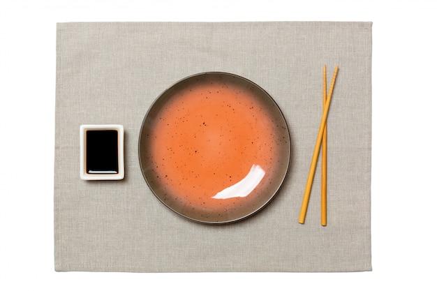 Pusty okrągły brązowy talerz z pałeczkami do sushi na szarym tle serwetka