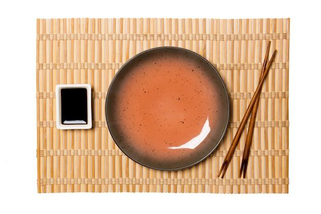 Pusty okrągły brązowy talerz z pałeczkami do sushi