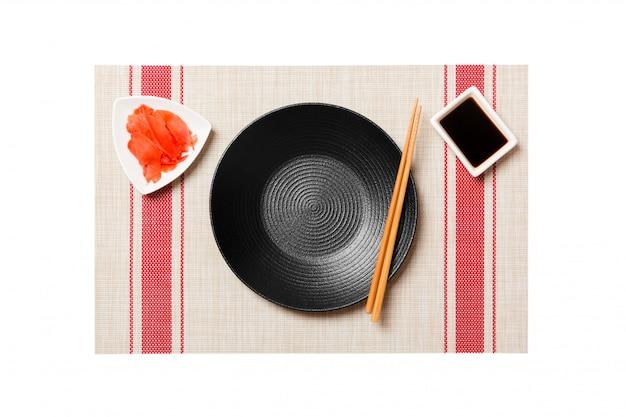 Pusty okrągły czarny talerz z pałeczkami do sushi