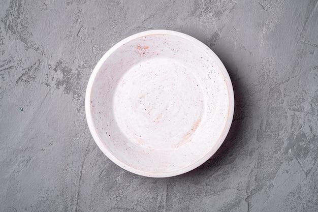 Pusty okrągły ręcznie biały drewniany talerz na kamiennym tle betonu, widok z góry