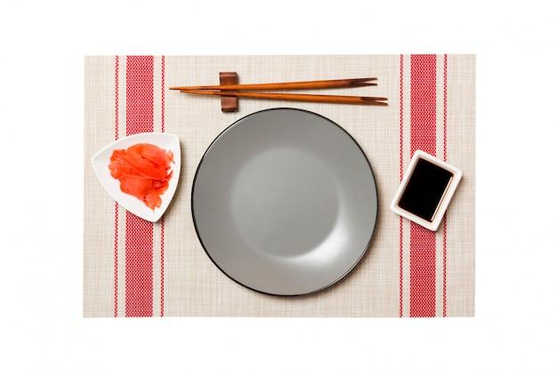 Pusty okrągły szary talerz z pałeczkami do sushi i sosu sojowego, imbir na matę sushi, widok z góry
