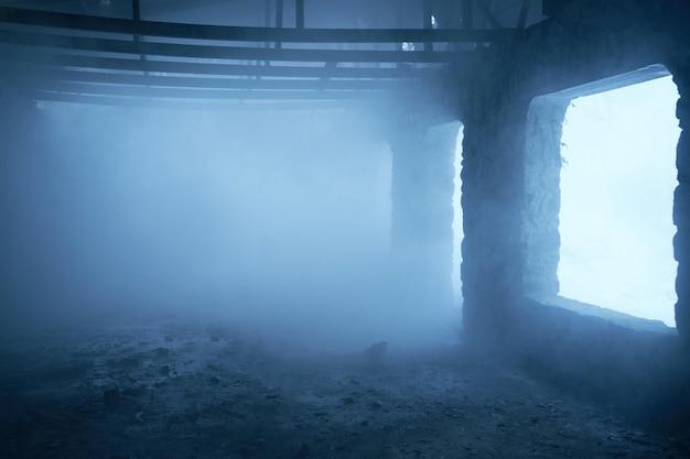 Pusty opuszczony zrujnowany budynek w środku w dymie i mgle