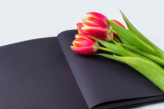 Pusty otwarty czarny pamiętnik (notatnik, szkicownik) ozdobiony wiosennymi czerwonymi tulipanami z miejscem na tekst lub napis. koncepcja pisania wspomnień, wspomnień, historii życia. kompozycja na dzień pamięci.
