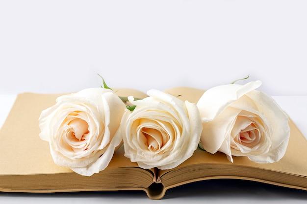 Pusty otwarty dziennik ozdobiony białymi różami z miejscem na tekst lub napis. koncepcja pisania listu, życzeń, celów, planów, historii życia.