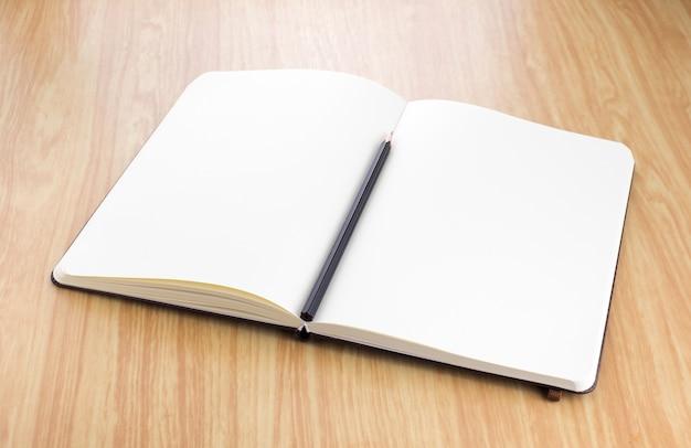 Pusty otwarty notatnik z czarnym ołówkiem na stół z drewna, szablon biznes makiety do dodawania tekstu