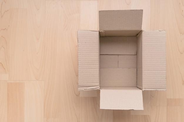 Pusty otwarty prostokątny karton na drewnianym tle