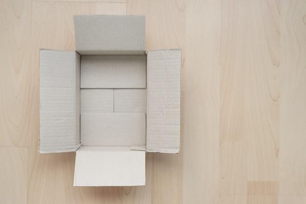 Pusty otwarty prostokątny karton na drewnie.