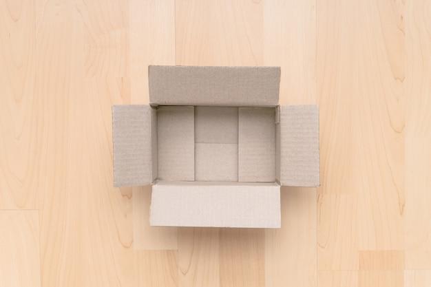 Pusty otwarty prostokątny karton na drewnie