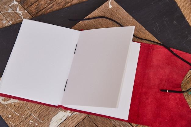 Pusty otwarty szkic książki dziennik z czerwoną skórą
