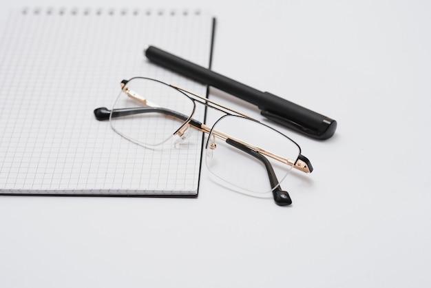 Pusty pamiętnik, długopis i okulary na białym tle