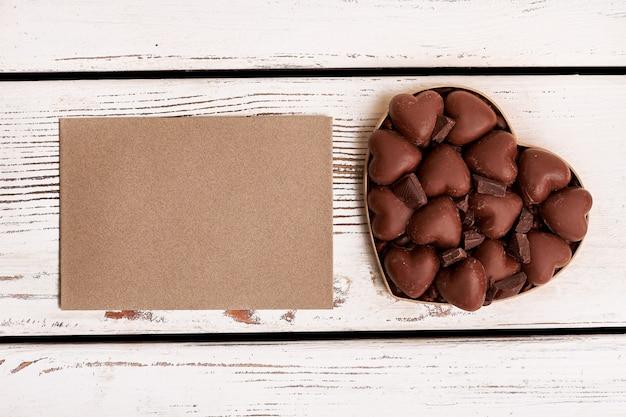 Pusty papier i czekolada. konfekcja na drewnianym tle. życzenie z głębi serca.