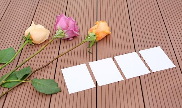 Pusty papier notatkowy z róża kwiatem i płatkami na drewnianym.