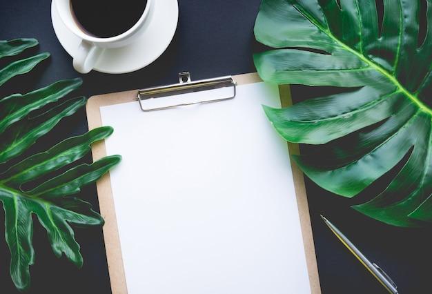 Pusty papier notatkowy z tropikalnymi liśćmi i akcesoriami na czarnym stole. biuro domowe, tła projektowe obszaru roboczego, płaskie lay, widok z góry