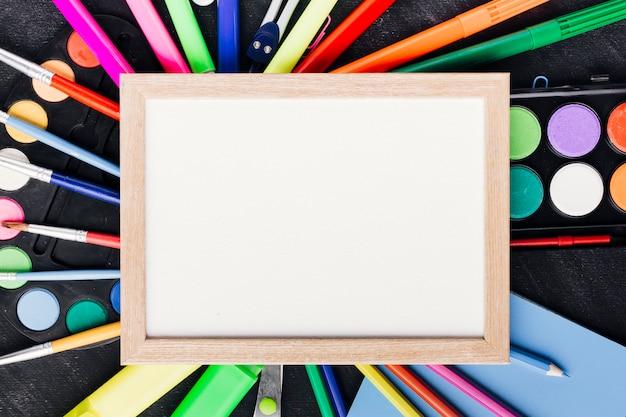 Pusty papier oprawione ułożone na kolorowe narzędzia do rysowania na tablicy
