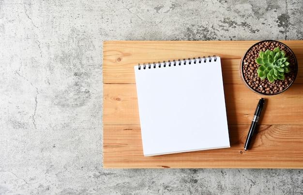 Pusty papier, sukulent i pióro na drewnianym stole z kopii przestrzenią