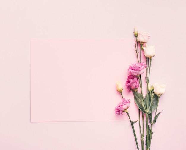 Pusty papier z jaskrawymi kwiatami na stole