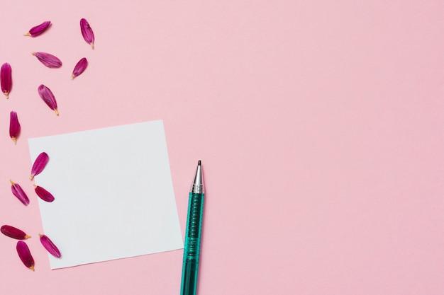 Pusty papier z płatkami kwiatów i długopis