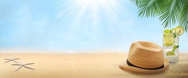 Pusty piasek z kapeluszem i napojem mojito na plaży krajobrazowej niewyraźne tło