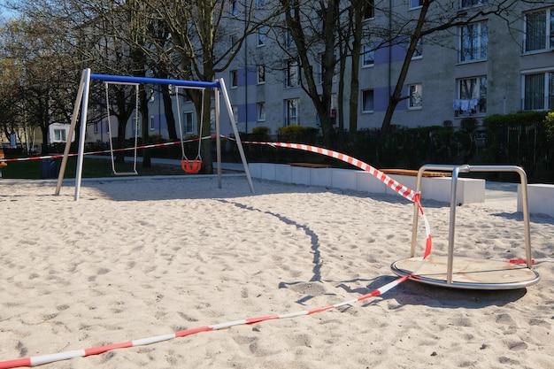 Pusty plac zabaw dla dzieci, zamknięty dla dzieci i rodziców. odetnij czerwoną białą taśmą ostrzegawczą w paski.