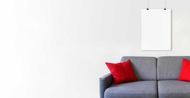 Pusty plakat wiszący na białej ścianie nad sofą. minimalistyczne tło wnętrza. baner poziomy