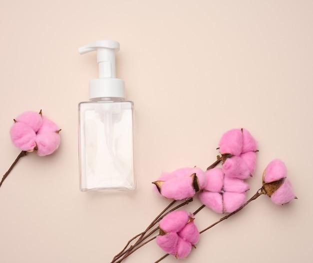 Pusty plastikowy pojemnik z dozownikiem na produkty płynne, mydło lub szampon na beżowym tle