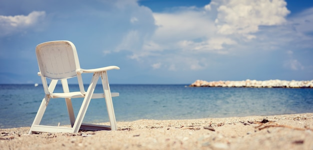 Pusty plażowy krzesło morzem z burzowymi chmurami w tle