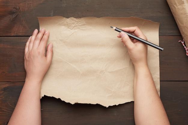 Pusty podarty arkusz brązowego papieru rzemieślniczego i dwie ręce z czarnym drewnianym ołówkiem