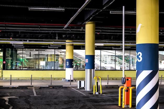 Pusty podziemny parking supermarketu. szlaban przy wejściu na parking jest podniesiony, nie ma samochodów.