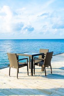 Pusty pokład patio i krzesło z niebieskim oceanem na malediwach