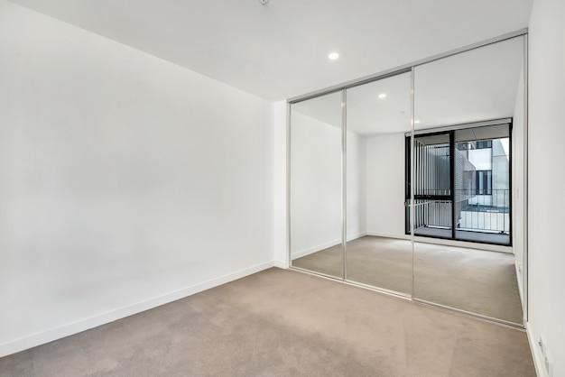 Pusty pokój z odbiciem okna w lustrzanej szafie