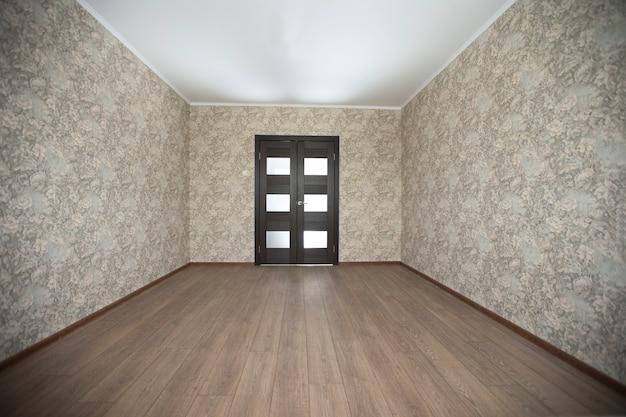 Pusty pokój z podłogami laminowanymi beżowymi ścianami w tle