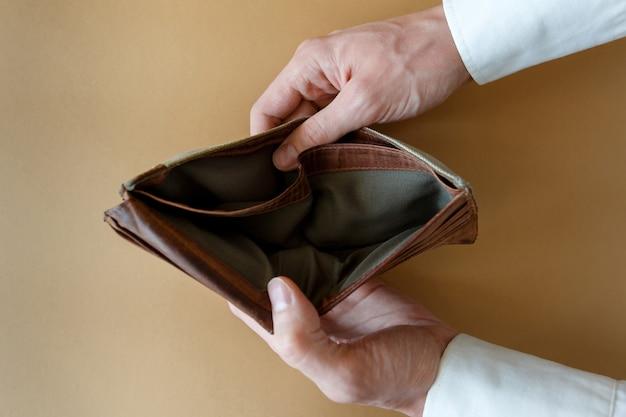 Pusty portfel w rękach człowieka. upadłość i niewypłacalność w gospodarce i finansach
