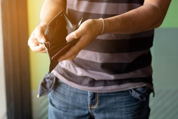 Pusty portfel w rękach człowieka.