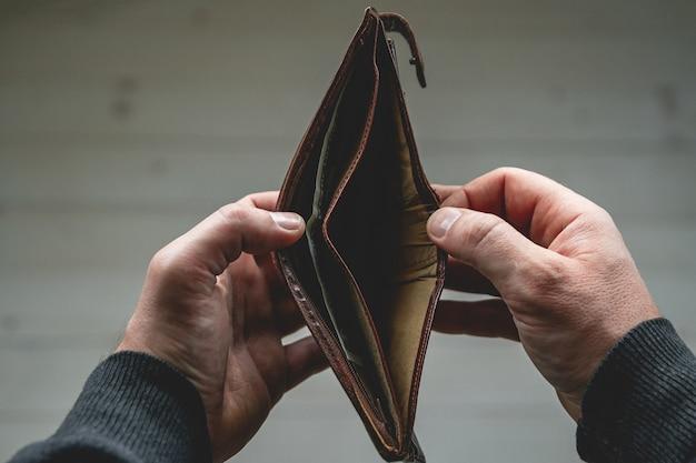 Pusty portfel w rękach młodego mężczyzny