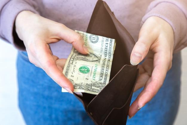 Pusty portfel z jednym dolarem. brak pieniędzy w torebce. kryzys gospodarczy, ubóstwo, pojęcie bezrobocia. konsekwencje izolacji osób z koronawirusem podczas kwarantanny. stopy inflacji. wzrost cen.