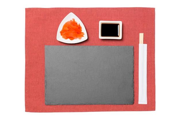Pusty prostokątny czarny łupek z pałeczkami do sushi, imbiru i sosu sojowego na tle czerwonej serwetki. widok z góry z miejscem na kopię do projektowania.