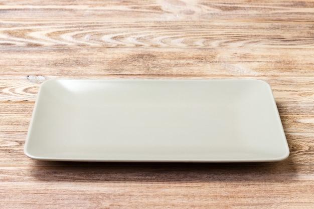 Pusty prostokątny talerz na drewnianym tle. widok z góry