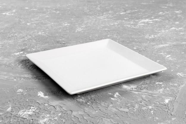 Pusty prostokątny talerz na popielatym stołowym tle