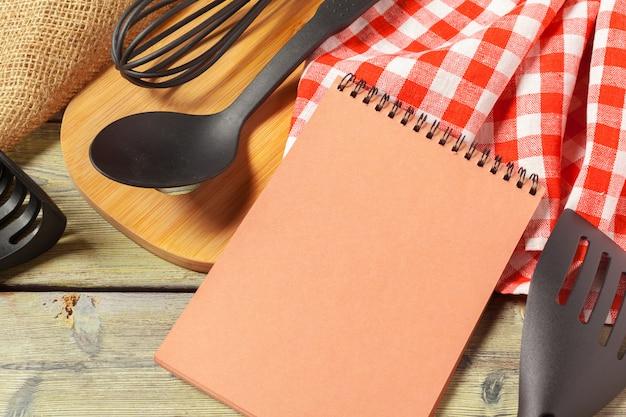 Pusty prześcieradło rozpieczętowany notepad i kuchenni naczynia na stole z tablecloth, kopii przestrzeń