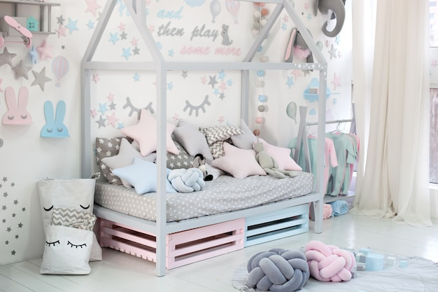 Pusty przytulny pokój dziecięcy z białą ścianą z naklejkami, zabawkami, łóżkiem z poduszkami. skandynawskie wnętrze pokoju dziecięcego. drewniane łóżko w kształcie domu z zabawkami i kocem. przedszkole