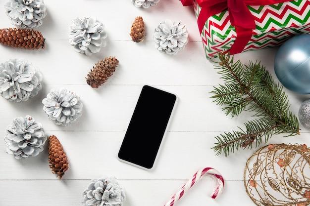 Pusty pusty ekran smartfona na białej drewnianej ścianie z kolorową dekoracją świąteczną i prezentami.