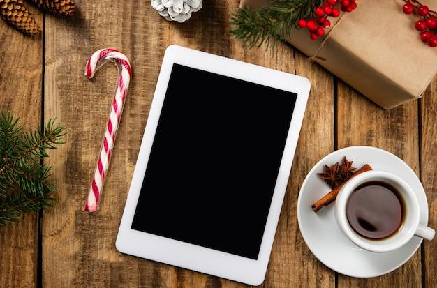 Pusty pusty ekran tabletu na drewnianej ścianie z kolorową dekoracją świąteczną, herbatą i prezentami.
