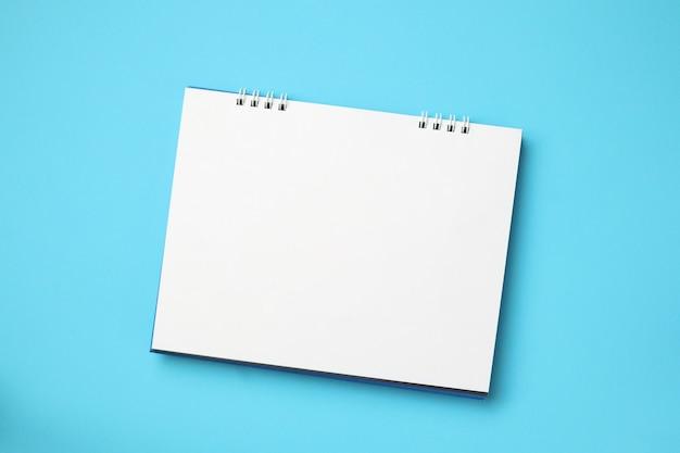 Pusty pusty kalendarz biały na niebieskiej ścianie