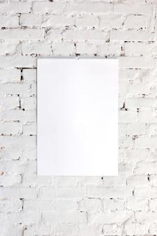 Pusty pusty obraz lub arkusz na białej ścianie z cegły. copyspace, negatywna przestrzeń dla twojej reklamy.