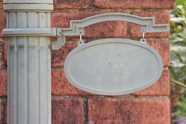 Pusty pusty stalowy signboard dla jakaś tytułu lub imienia z ściana z cegieł tłem