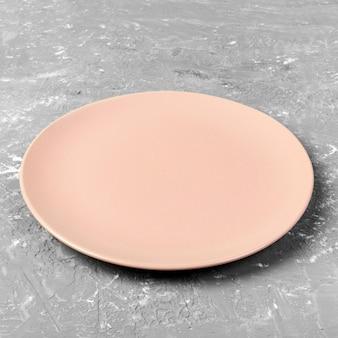 Pusty różowy lub koralowy okrągły talerz na szarym tle tabeli cementu.