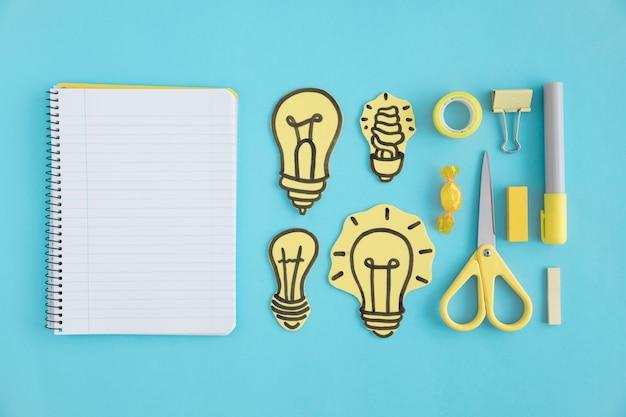 Pusty ślimakowaty notatnik z papierowymi żarówkami i materiały na błękitnym tle